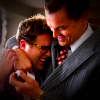 Jonah Hill and Leonard DiCaprio embrace and laugh in The Wolf of Wall Street