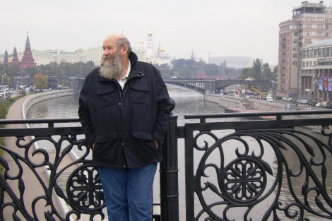 Howard Willis stands on a bridge, in the background are Moscow River and the Kremlin. The large building on the right is the infamous House on the Embankment, where Stalin's elite lived and where the NKVD knocked on doors late of nights in 1937–8.