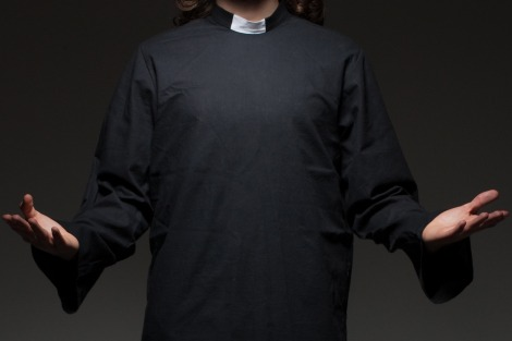 Priest in dog collar with hands spread