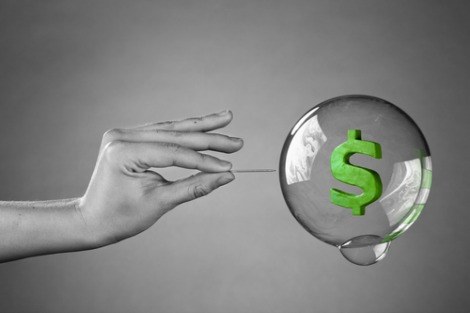 Hand with pin bursting a bubble containing a dollar sign