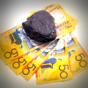 Wad of Australian $50 bills weighed down by a lump of coal