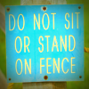 Blue sign, 'Do not sit or stand on fence'