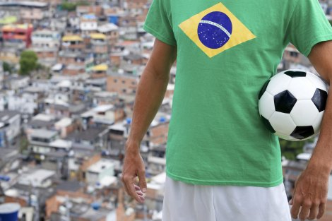Brazilian football player stands in Brazilian flag t-shirt holding soccer ball in front of favela background in Rio de Janeiro