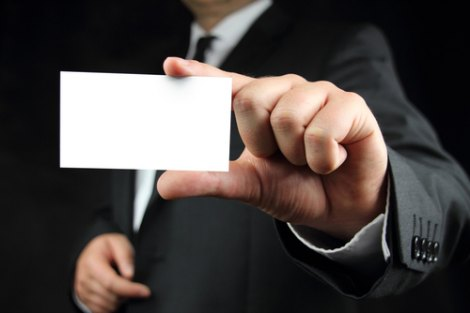 Man in suit holds up blank business card