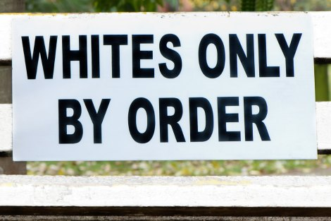 'Whites only by order' sign attached to a park bench