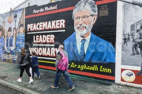 A family walks past a mural in honour of Gerry Adams