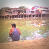 Man crouches beside river in Cambodia