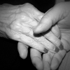 Older hand clasped by younger