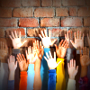 Raised hands in front of brick wall
