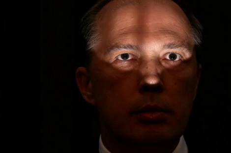Peter Dutton's face in shadow