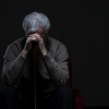 Elderly man, head down in shadows