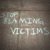 Stop blaming victims chalk slogan