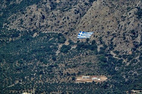 Greek flag on mountainside