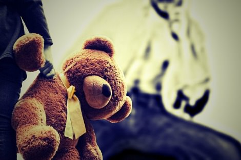 Child with teddy bear observed by threatening adult