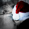Kid in Santa hat looks out rainy window