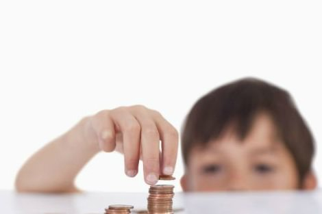 young boy stacking coins