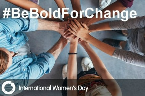 International Women's Day photo shows people in a circle with hands joined in solidarity