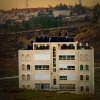 A home in al-Bireh contrasted with the settlement of Psagot in the background. Note the water tanks.