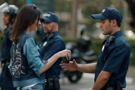 Kendall Jenner hands Pepsi to police officer