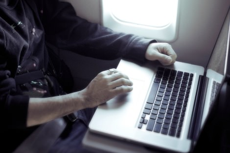 Person using laptop on a plane