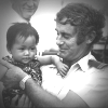 Frank Dalton holding a Vietnamese refugee child, Xye Than Hueon the deck of the Tu Do in Darwin, November, 1977. National Library of Australia