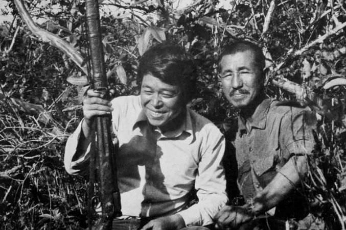 Norio Suzuki poses with Onoda and his rifle after finding him in the jungles of Lubang Island.