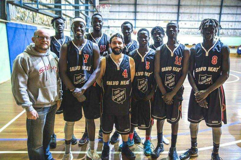 Troy Pittaway with basketball team consisting of young Sudanese men