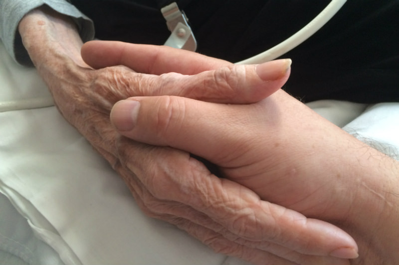 Holding hands with sick old woman