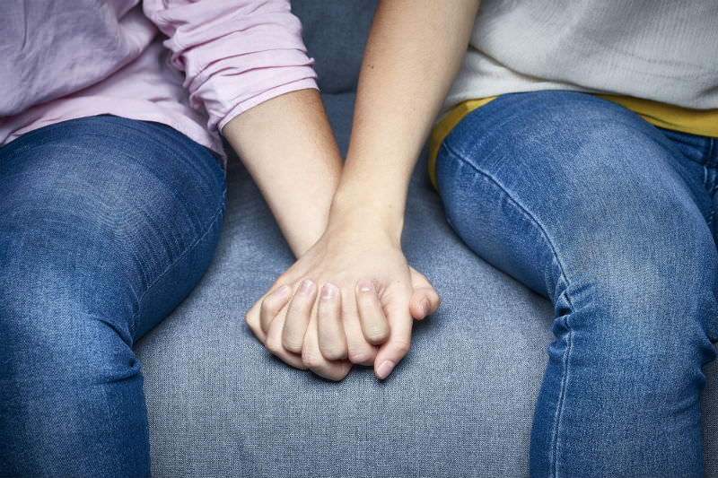 Partial view of lesbian couple holding hands on couch (Getty)