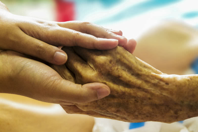 Holding the hand of an old person