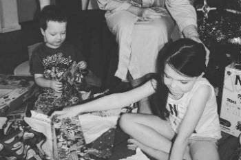 Amy Thunig and her children opening presents under a Christmas tree.