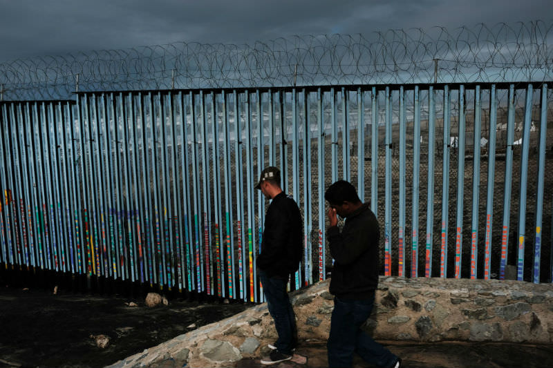 Two men walk along a border fence that stands along a beach in the city of Tijuana. (Spencer Platt/Getty Images)