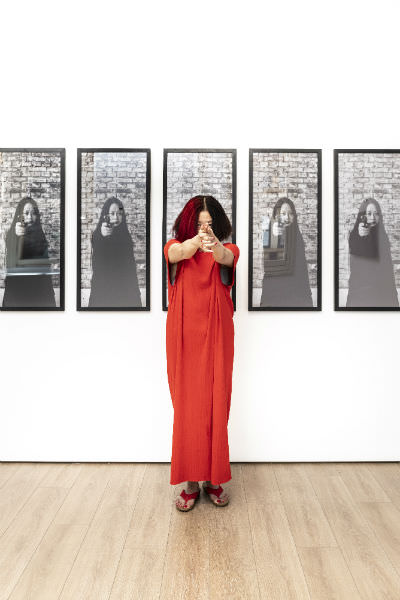 Xiao Lu, 2019, pictured in front of her work 15 Gunshots… From 1989 to 2003«15?...?1989? 2003» , 2003, 15 black and white digital prints, framed and then punctured by a bullet. 100 x 45 x 15 cm, printed in 2018, edition 12/15. Photographs by Li Songsong. Courtesy of the artist. Installation view at 4A Centre for Contemporary Asian Art, January 2019; photograph: Kai Wasikowski, 2019, for 4A Centre for Contemporary Asian Art.