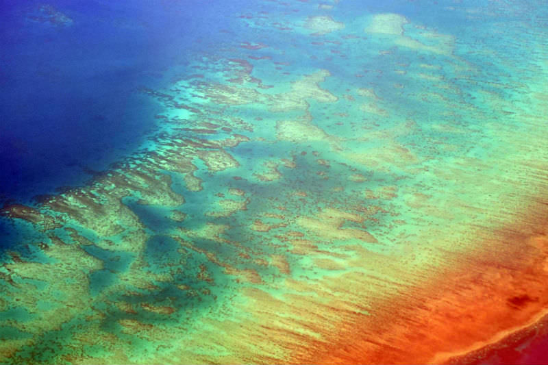 Aerial photo of a portion of the Great Barrier Reef off the coast of Cairns, Qld, Australia, which shows evidence of bleaching (Mangiwau / Getty Creative)
