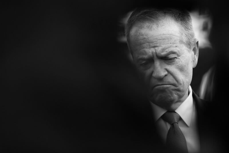 Bill Shorten, partially obscured by silhouettes of people in the foreground, looks pensive as he campaigns in Sydney in May 2019. (Photo by Ryan Pierse/Getty Images)