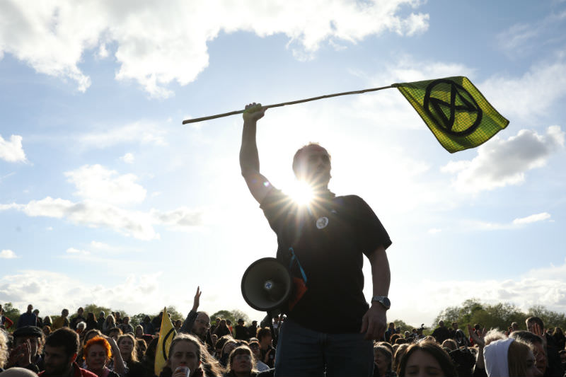 An Extinction Rebellion campaigner waves a flag in Hyde Park in London in April 2019. (Photo by Dan Kitwood/Getty Images)