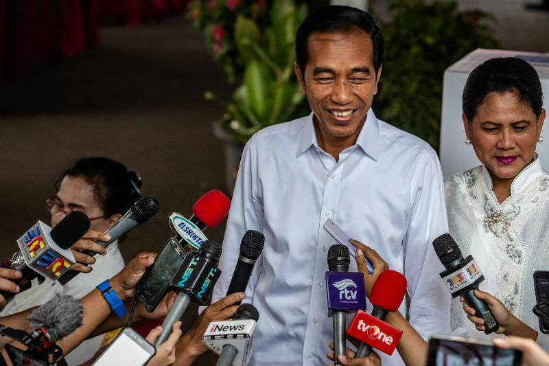 Indonesian President Joko Widodo and his wife Iriana speak to journalists after casting his ballot at a polling station on 17 April 2019 in Jakarta. (Photo by Ulet Ifansasti/Getty Images)
