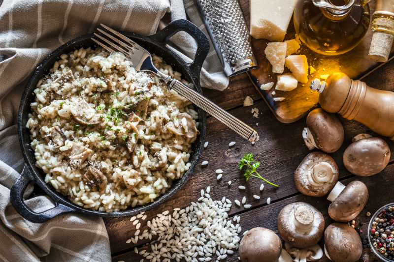 Risotto fungi porcini on rustic wooden table (photo by fcafotodigital via Getty)