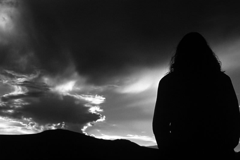 Person silhouetted against a sky that is both bright and dark. By gaiamoments via Getty
