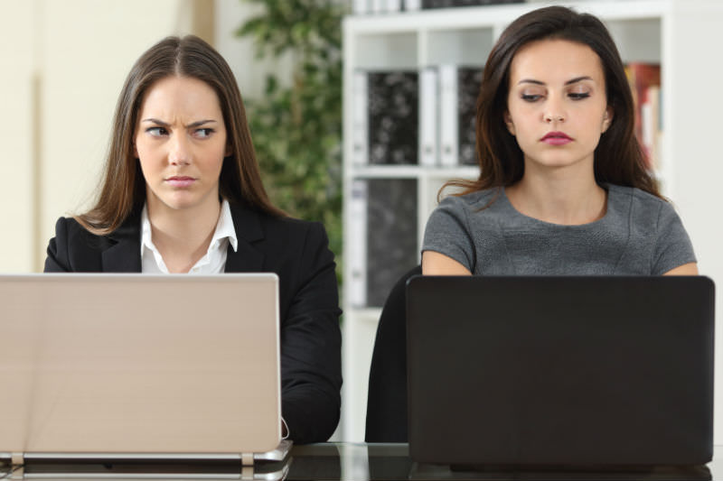 Women with laptops looking at each other with anger and suspicion. Photo by Antonio Guillem via Getty
