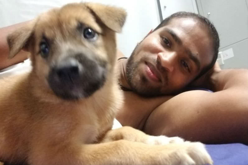 Shamindan Kanapathi, pictured with one of the camp dog puppies from Manus Island. Published with permission.