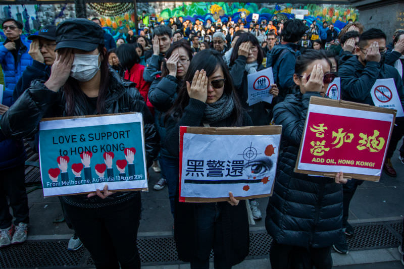 Pro-Hong Kong demonstrators cover one eye in reference to the bloodied eye patch, another symbol of the Hong Kong protests, in Melbourne on 31 August 2019 in Melbourne. (Photo by Asanka Ratnayake/Getty Images)
