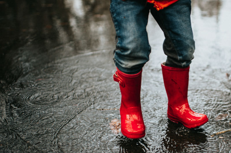 Child in red gumboots standing in a puddle. (Catherine Falls Commercial / Getty)