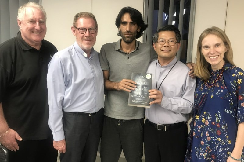 Members of the Catholic delegation to PNG pictured with Behrouz Boochani (centre). Boochani can be seen presenting a copy of his book No Friend but the Mountains to Bishop Vincent Long of the Diocese of Parramatta.