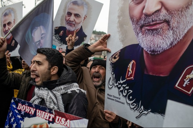 People hold posters showing the portrait of Iranian Revolutionary Guard Major General Qassem Soleimani and chant slogans during a protest outside the US Consulate on 5 January 2020 in Istanbul, Turkey. (Photo by Chris McGrath/Getty Images)